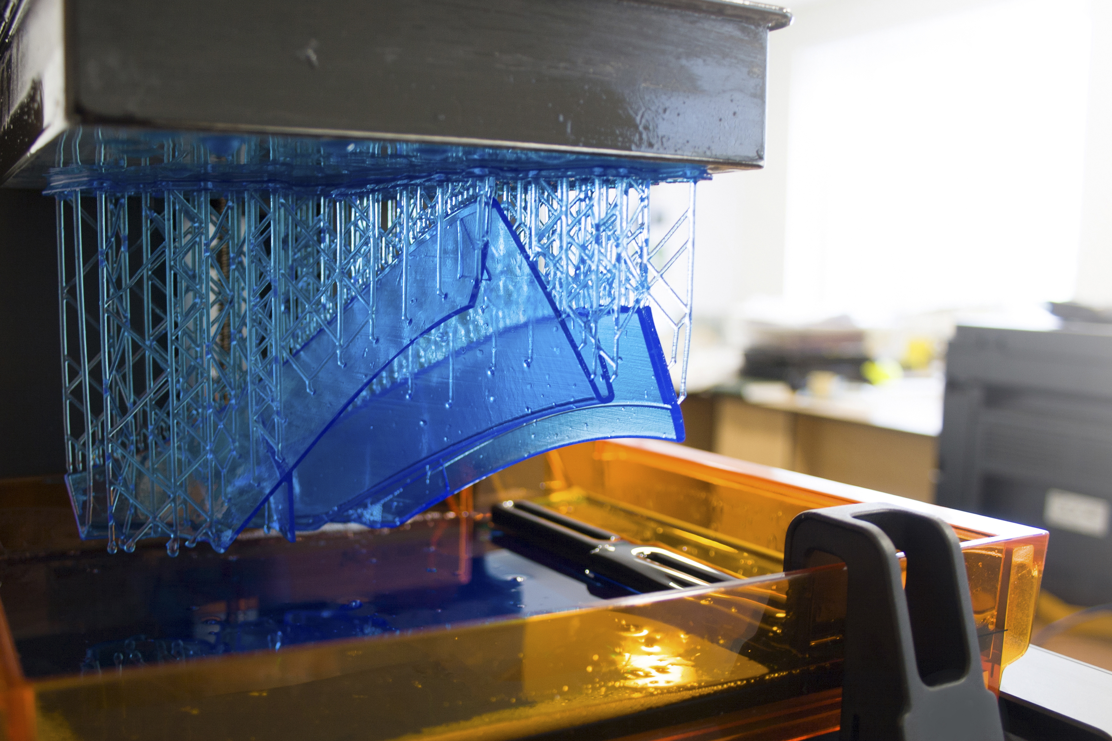 A blue plastic part printed by a 3D printer using supports